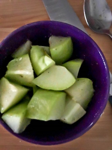 The 4 chayote squash sections cut into chunks in a purple bowl.