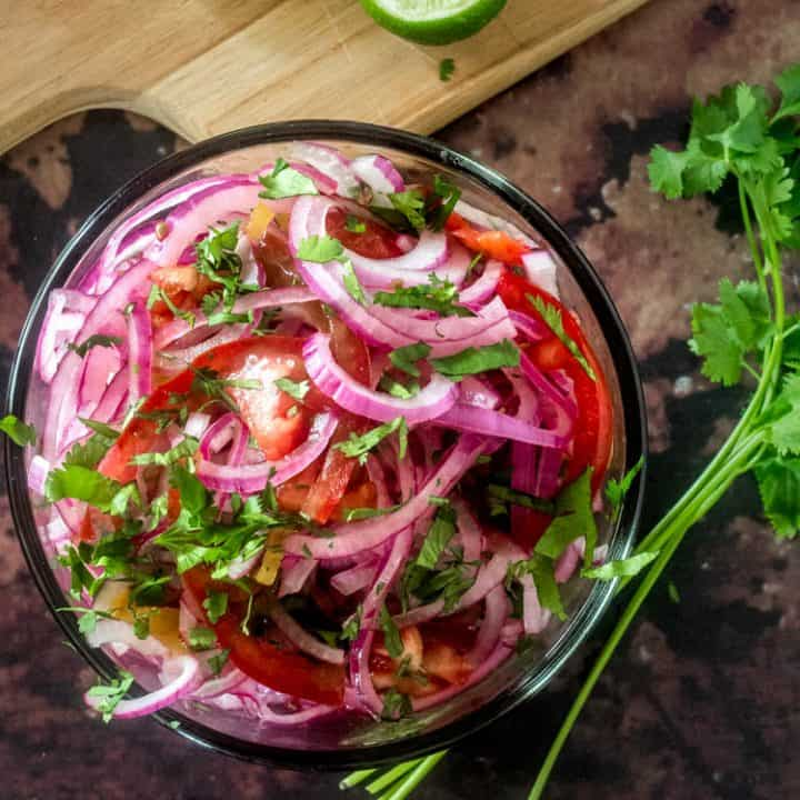 Peruvian Red Onion and Tomato Salad bird's eye view with fresh cilantro spring.