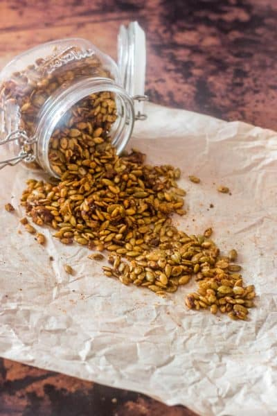 Easy Spiced Candied Pepitas spilling from a glass jar onto parchment are a healthy, gluten free, vegan snack.