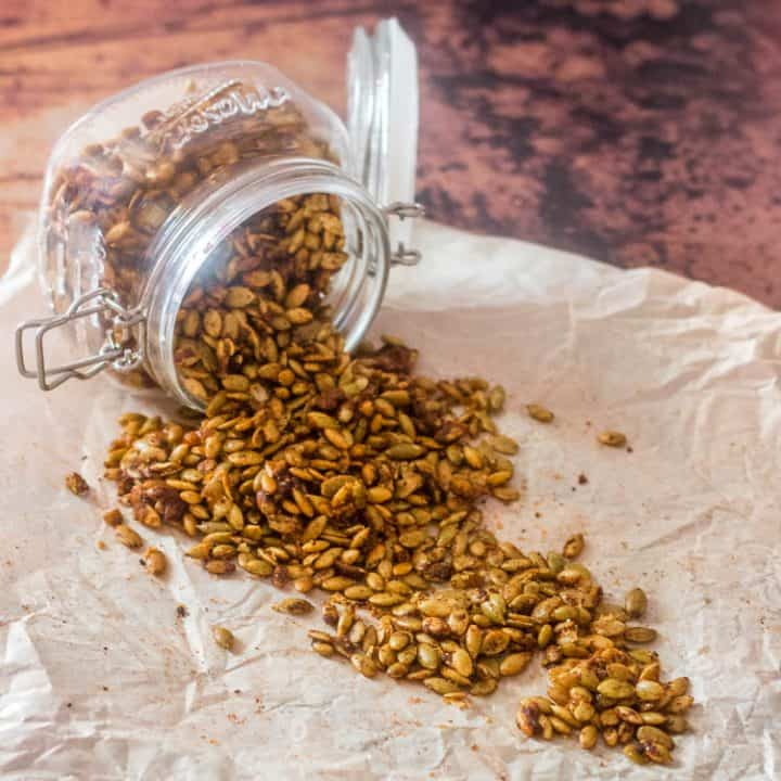 Easy Spiced Candied Pepitas spilling from a glass jar with a hinged lid.