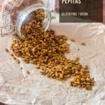 Easy Spiced Candied Pepitas tumbling out of a glass jar onto a sheet or parchment are gluten free, vegan, and healthy!