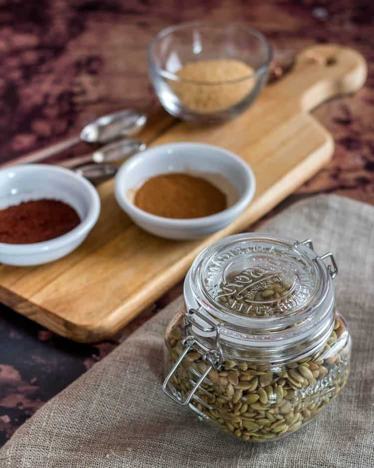 Easy Spiced Candied Pepitas ingredients including roasted and salted pepitas in a glass jar, spices, and raw sugar on a cutting board.