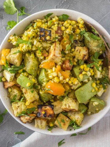 A white salad bowl of Grilled Mexican Panzanella Salad with chayote squash, corn, Mexican cheese, and cilantro lime vinaigrette with a copper serving spoon.