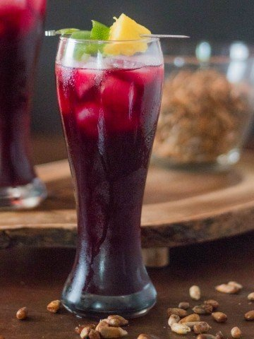 2 glasses of chicha morada with ice garnished with pineapple and lime twist with a bowl of cancha.