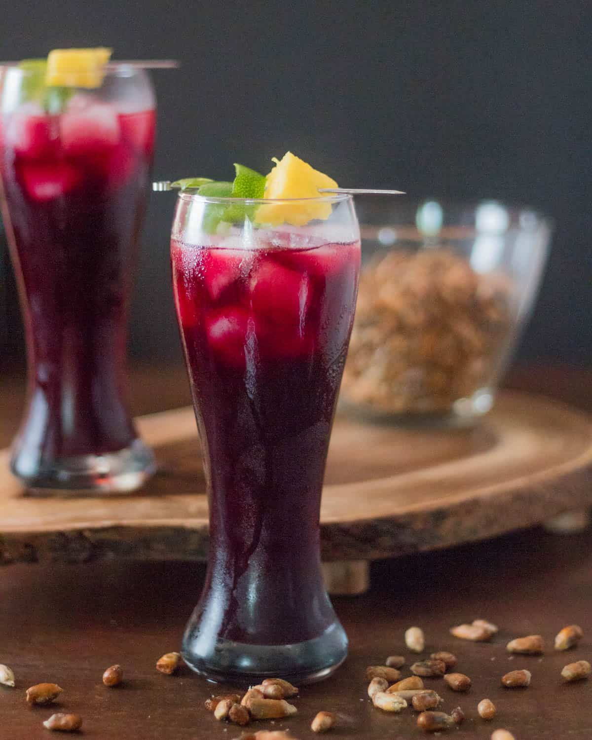 2 glasses of Peruvian chicha morada, a bowl of cancha, on a wood cutting board with a dark background.
