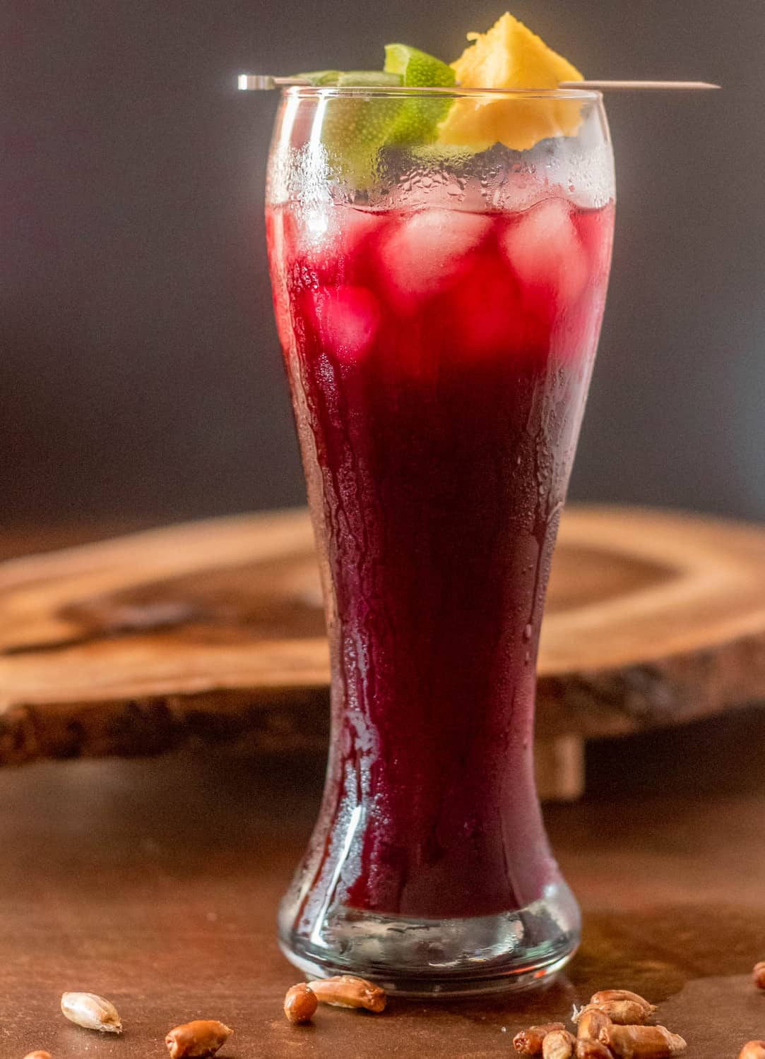 A close up of Peruvian chicha morada (purple corn drink) in a tall pilsner glass with lime twist and pineapple wedge.