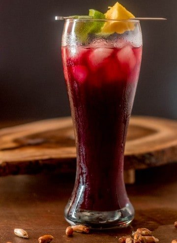 Peruvian Chicha Morada with fruit garnish in a tall, clear pilsner glass with cancha (corn) scattered around.
