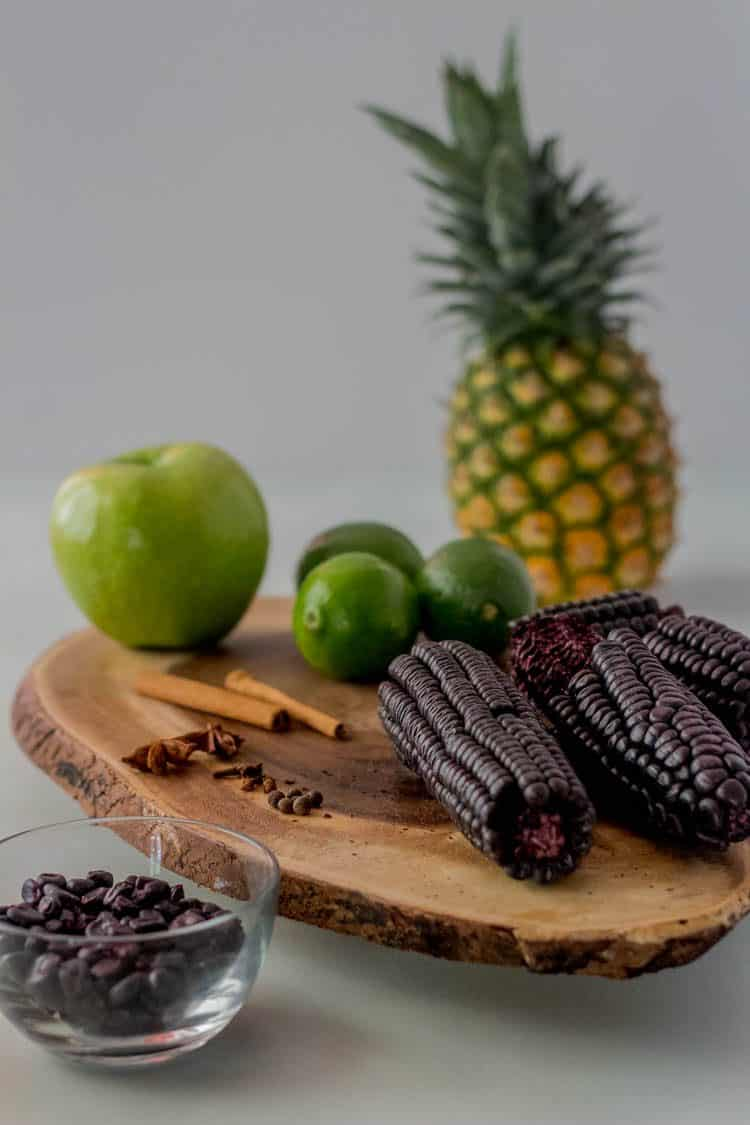Ingredients for chicha morada: pineapple, maiz morado (dried purple corn), apple, limes, spices, on a wood cutting board.