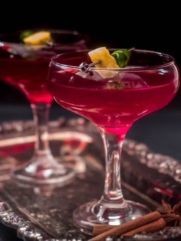 A gorgeous red-violet hued Chicha Morada and Pisco Cocktail garnished with a pineapple bit and a lime twist in a coupe glass... a truly unique cocktail!