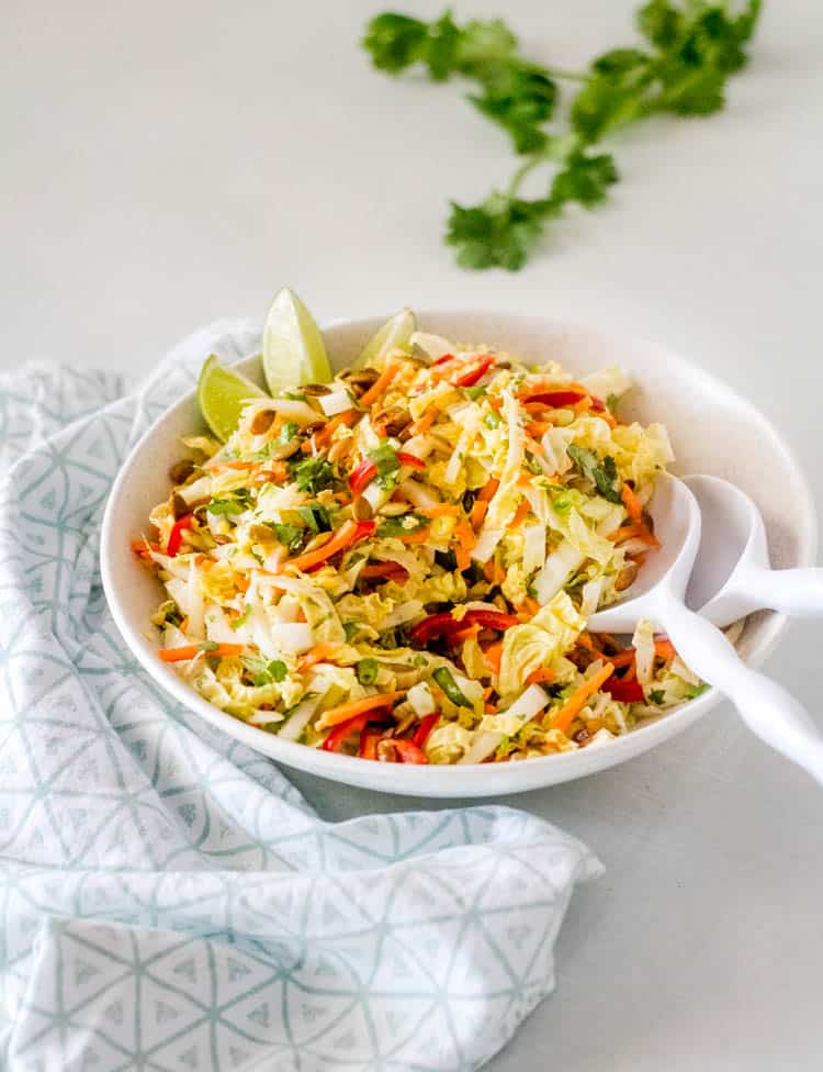Healthy Mexican Coleslaw with Passion Fruit Dressing garnished with pepitas and lime wedges in a round white bowl with white salad servers and a print napkin.