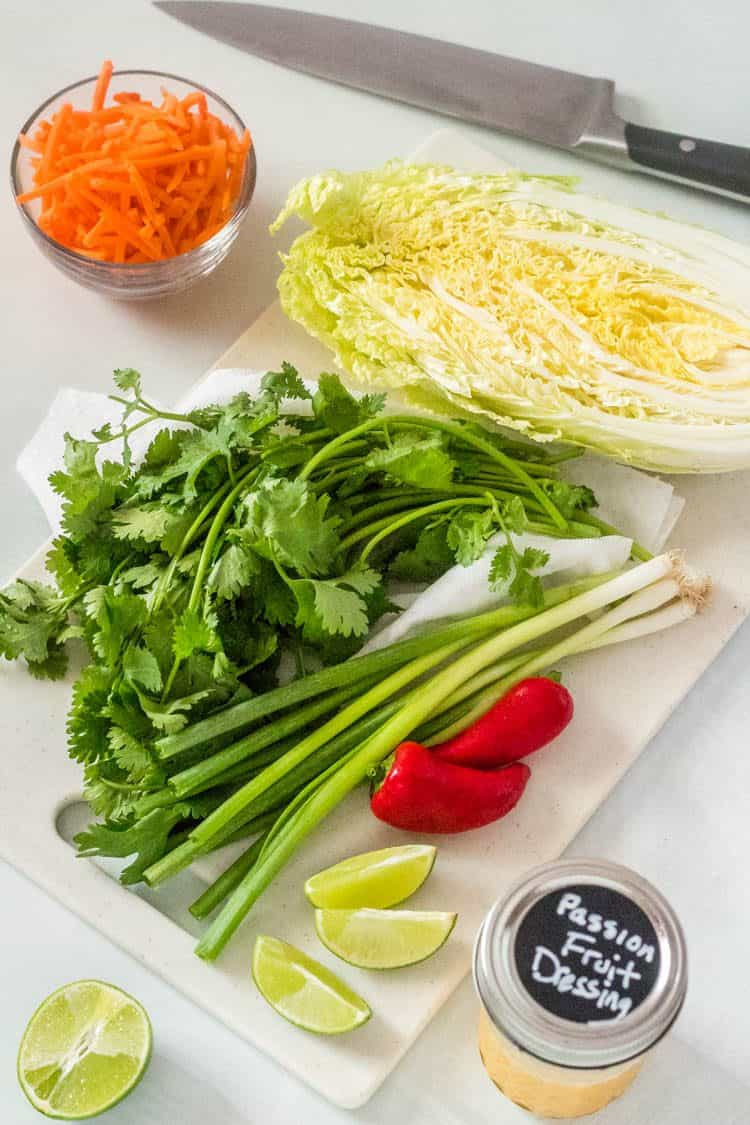 Ingredients for Healthy Mexican Coleslaw with Passion Fruit Dressing: napa cabbage, cilantro, scallions, Fresno peppers, limes, shredded carrots, and Passion Fruit Dressing on a white cutting board with a knife. A quick and easy vegetarian salad!