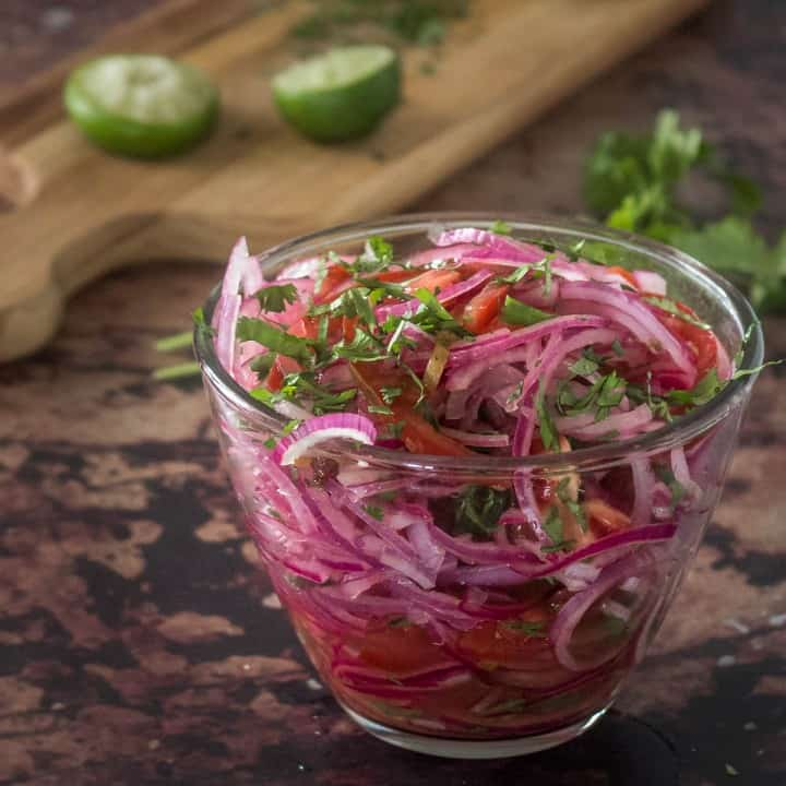 A clear glass bowl of salsa criolla (Peruvian red onion tomato salad) on a brown background with limes and cilantro.