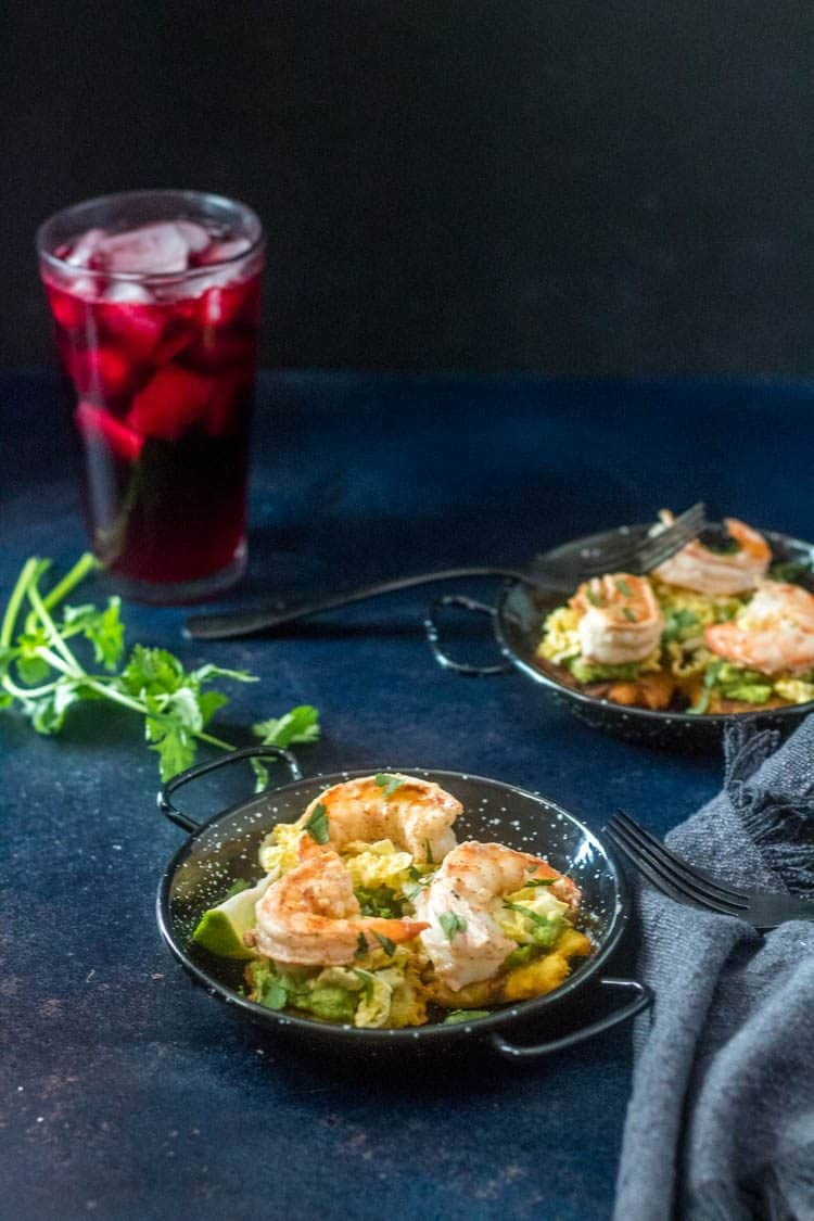Lovely tropical Tostones with Shrimp, Avocado, and Passion Fruit Slaw on 2 mini paella pans with fresh cilantro sprig and chicha morada with ice.