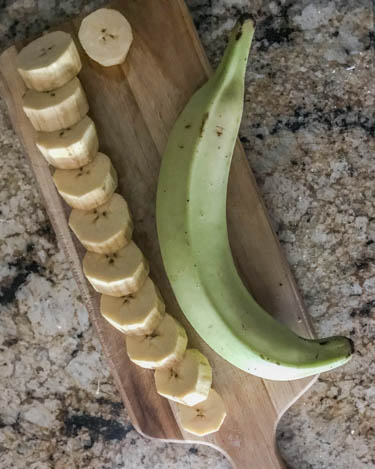 In preparation for tostones, a cutting board with 1 sliced plantain and 1 unpeeled plantain.