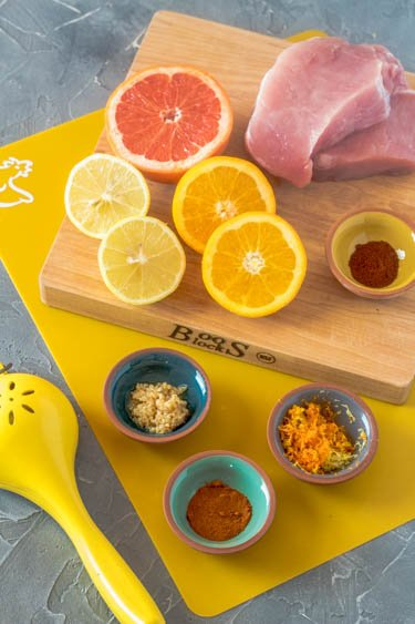 Halved citrus - lemon, orange, grapefruit - along with garlic and spices for the Citrus Marinated Pork Chop with Hatch Chile on a yellow cutting board.