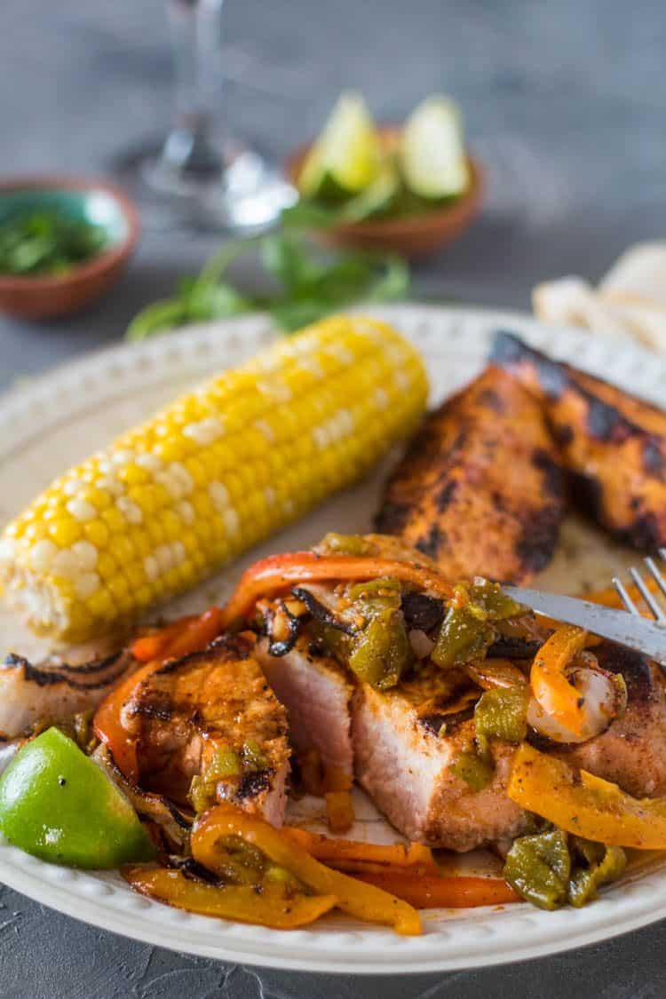 Citrus Marinated Pork Chop with Hatch Chile, sweet pepper, and sweet onion on a plate with grilled corn and grilled sweet potato wedges, fork and sharp knife.