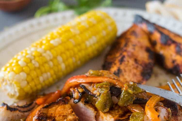 Citrus Marinated Pork Chops with Hatch Chile on a cream colored plate with grilled corn, lime wedge, grilled sweet potato wedges.