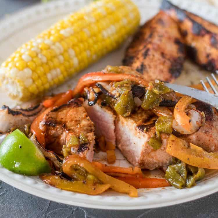 1 Citrus-Marinated Pork Chop with Hatch Chile sliced through with grilled corn and sweet potato wedges on a white plate close up.