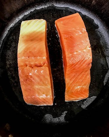 2 salmon portions in a black cast iron skillet being seared.