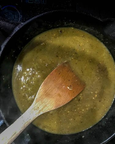 The puréed tomatillo sauce, garlic, cumin frying in a cast iron skillet.