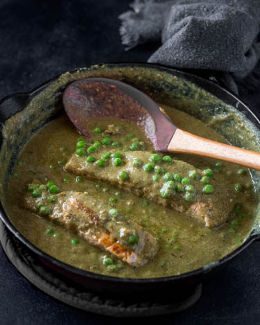 Seared salmon portions are added back into the mole verde sauce and peas.