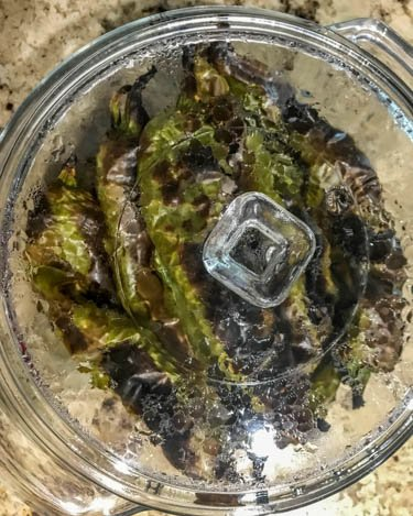 7 charred Hatch chiles in a glass covered casserole to steam.
