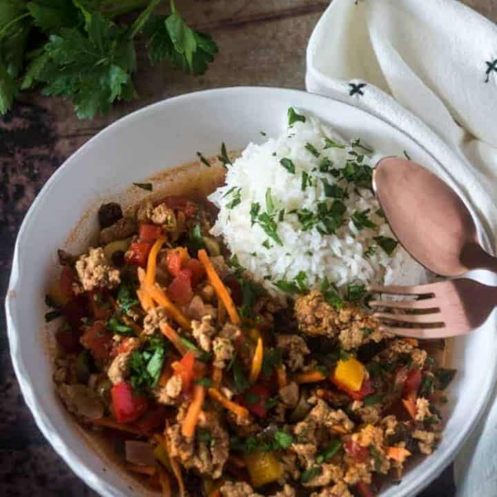 Healthy Picadillo with Cuban flavors in a white ceramic bowl with white rice and chopped parsley, linen napkin, and copper flatware.