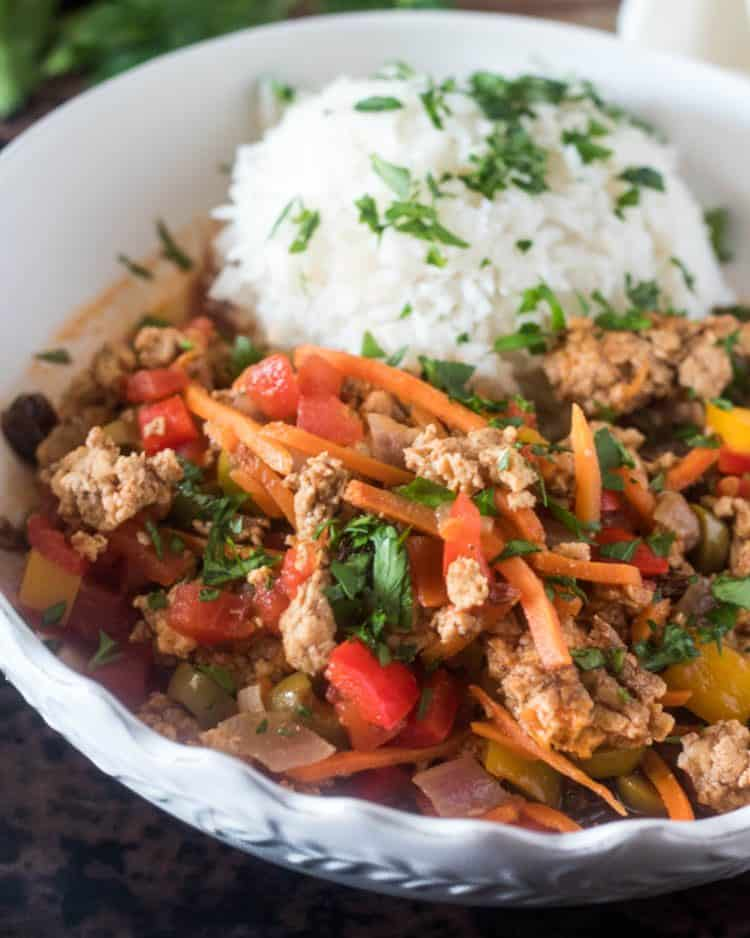 A close up of Healthy Picadillo in a white ceramic bowl with white rice and fresh parsley.