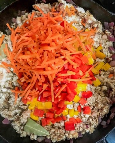 Shredded carrots and sweet bell pepper are added to the ground meat mixture.
