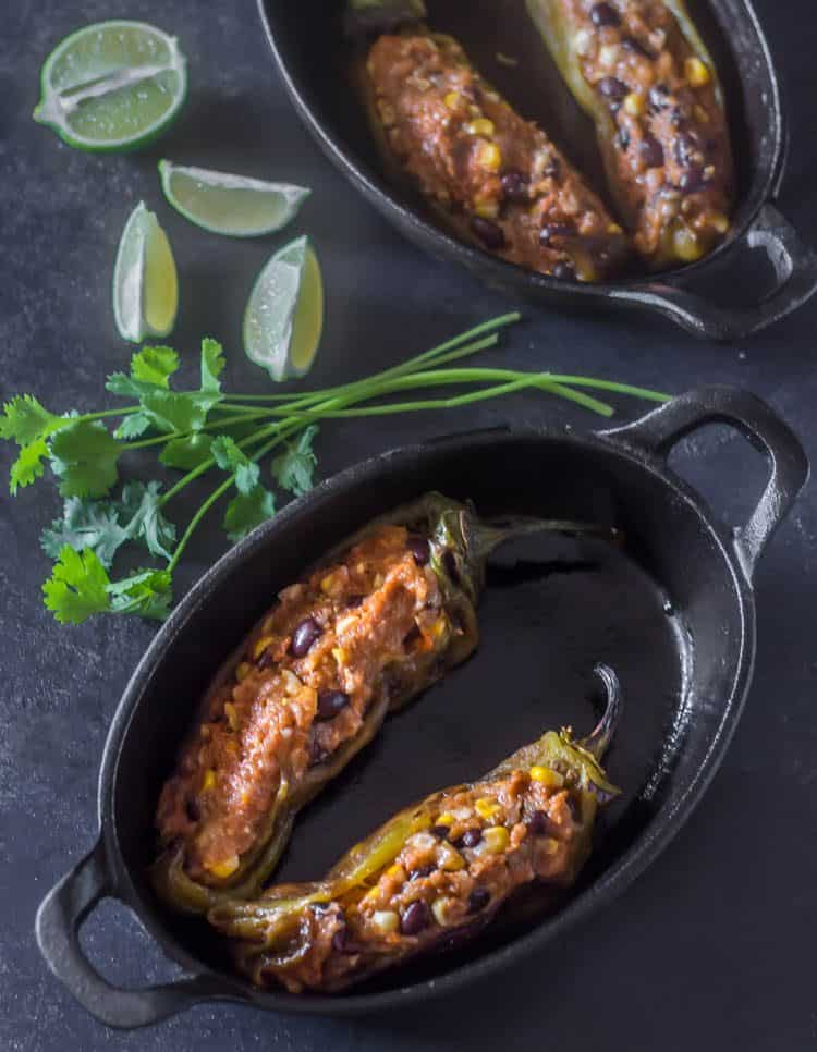 2 oval cast iron baking dishes with 2 Hatch green chiles stuffed with the ground turkey and chorizo mixture that includes corn, black beans, and spices (similar to a meatloaf).