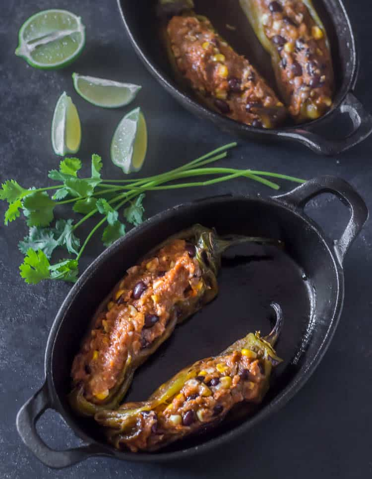 2 oval cast iron baking dishes with 2 Hatch green chiles stuffed with the ground turkey and chorizo mixture that includes corn, black beans, and spices (similar to a meatloaf), before cooking.