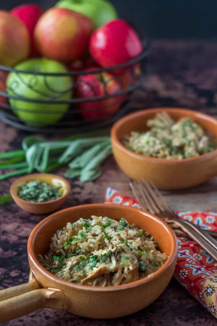 2 yellow ceramic bowls with Instant Pot Pork and Apples in front of a bowl of apples with fresh sage and chives.