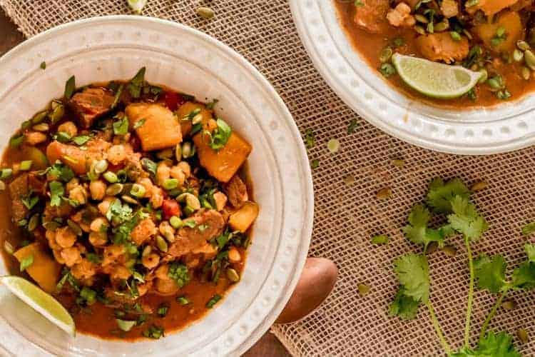 Mexican Pumpkin Stew with Pork and Hominy in a white bowl with lime wedge and cilantro.