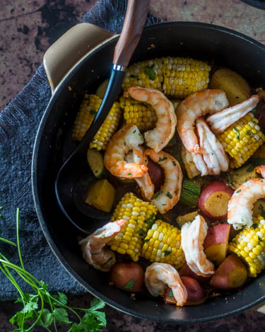 Mexican Shrimp Boil with large shrimp, fresh corn, tiny red potatoes, and Mexican grey squash in a cast iron pot with fresh cilantro.