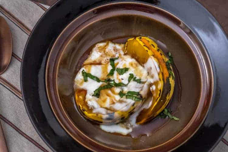 Candied Pumpkin in Spiced Syrup in a bronze ceramic bowl topped with yogurt and fresh mint.