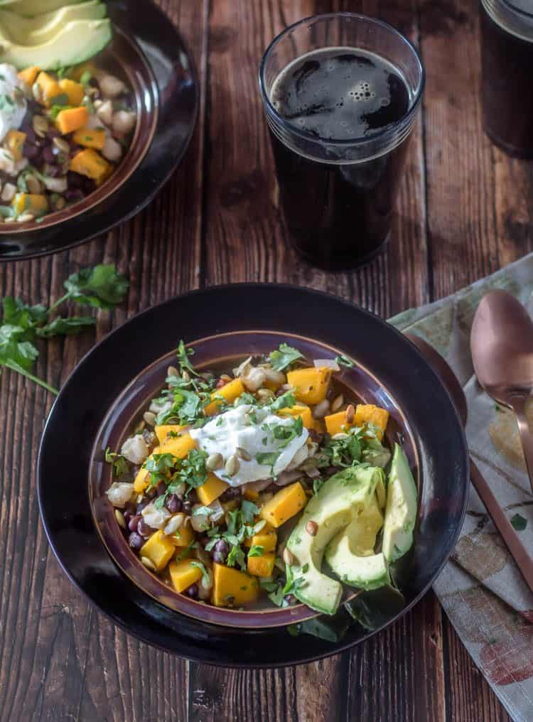 Vegetarian Pumpkin Posole with roasted pumpkin, hominy, Hatch green chile, and Mexican spices in a bronze ceramic bowl with avocado slices, a dollop of yogurt, pepitas, and cilantro.