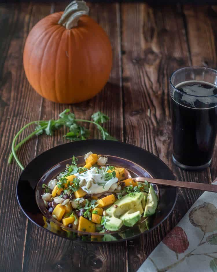 Vegetarian Pumpkin Posole in a bronze bowl with a copper spoon, autumn colors napkin, dark beer, and fresh cilantro.