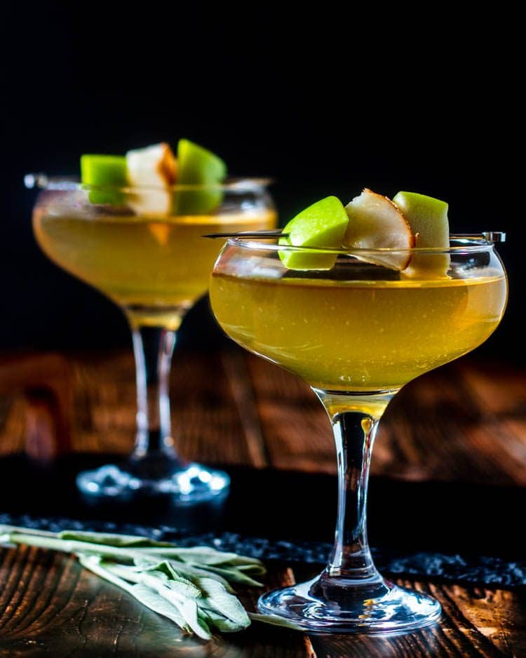 2 lovely Apple and Pear Martinis in coupe glasses on a slate tray, wood background, with fresh sage... a perfect unique, fall cocktail.