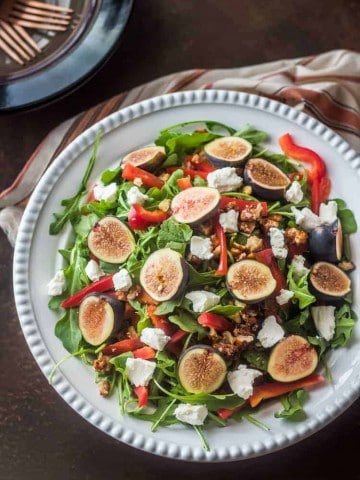 Fig and Arugula Salad with chevre and candied walnuts in a white ceramic bowl, a perfect fall salad that's gluten free and vegetarian.