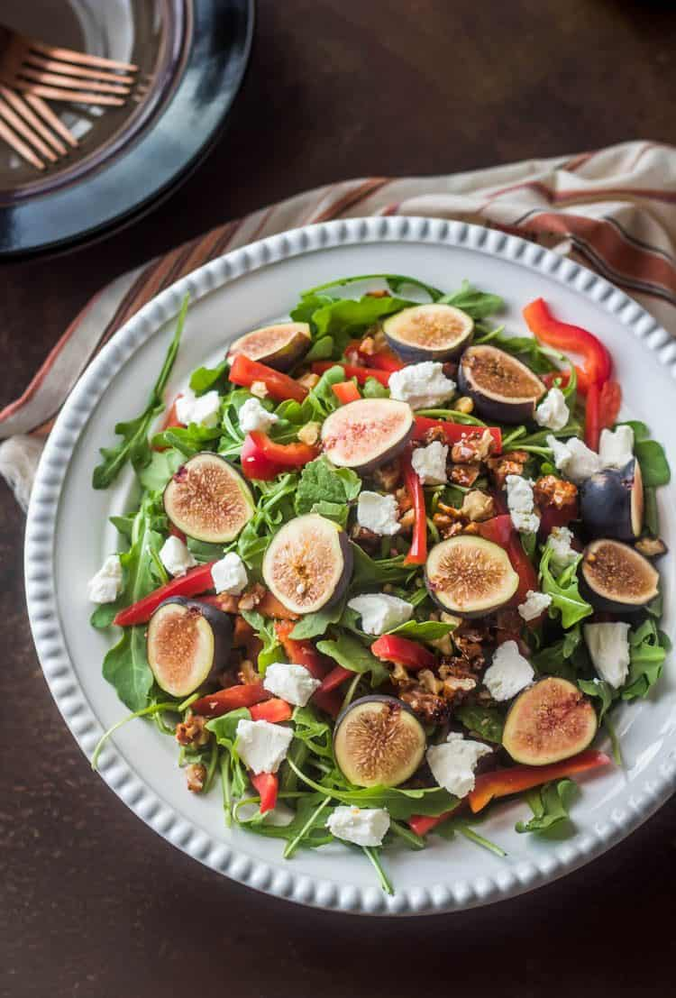 Fresh arugula and Mission figs tossed with chevrè, candied walnuts, sweet red pepper, and a simple fig vinaigrette... in a white ceramic bowl with striped napkin. A perfect fall salad!
