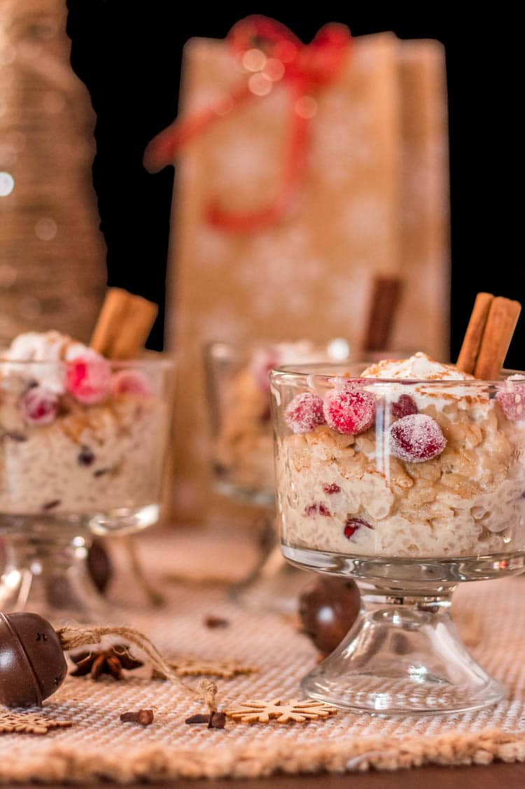 2 glass trifle bowls with gluten free and dairy free Instant Pot Arroz con Dulce (Puerto Rican Rice Pudding) with cinnamon sticks, candied cranberries, and Christmas decorations.