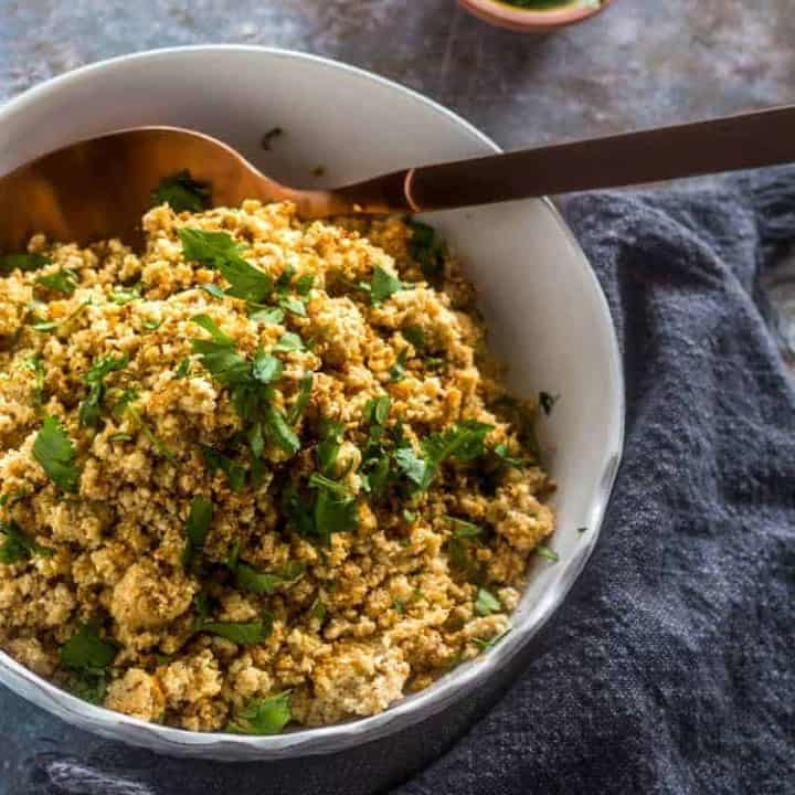 Vegan and gluten free Healthy Mexican Roasted Cauliflower Rice in a white ceramic serving bowl with copper spoon, a small bowl of chopped cilantro on a grey background.