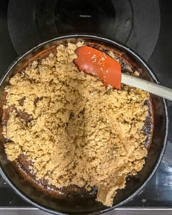 The cauliflower rice spread thin on a baking pan before going in the oven.