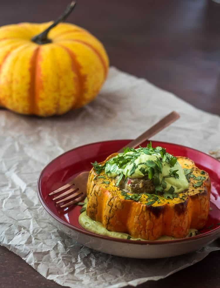 A serving of Healthy Southwest Stuffed Acorn Squash topped with avocado crema and chopped cilantro on a red ceramic plate with copper fork.
