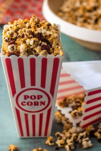 A tall red and white popcorn bag with Sweet Tajín Popcorn spilling over, a big bowl of popcorn in the back, and bright cloth napkin.