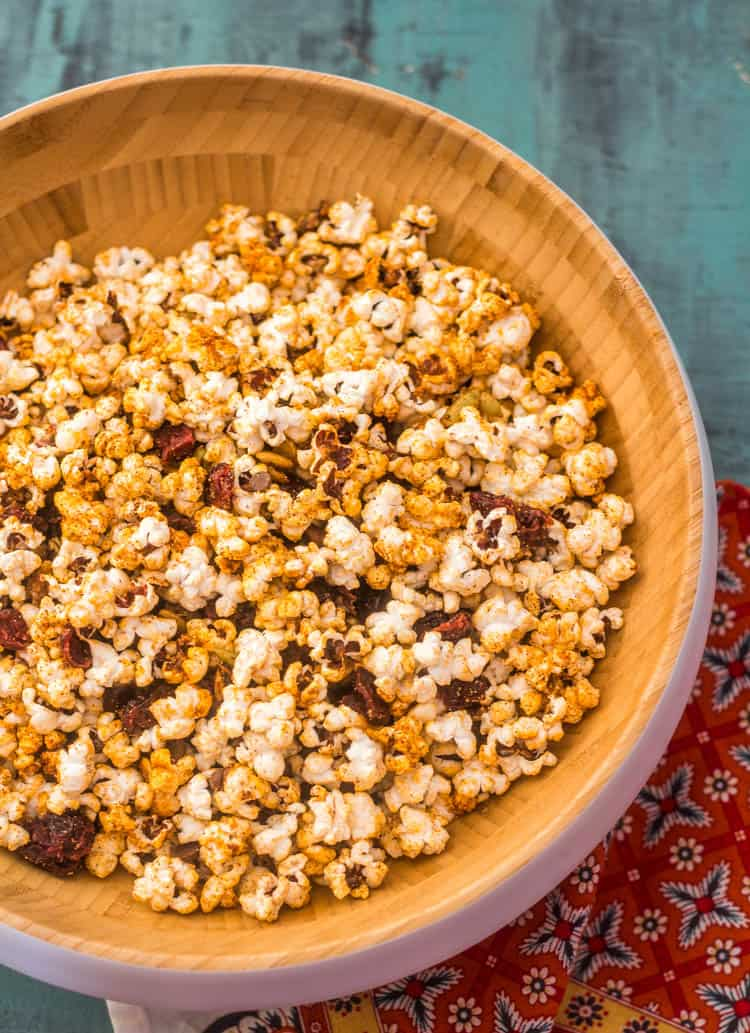 A close up of Sweet Tajín Popcorn with dried cranberries, chocolate, spiced candied pepitas in a wood bowl on a blue background.