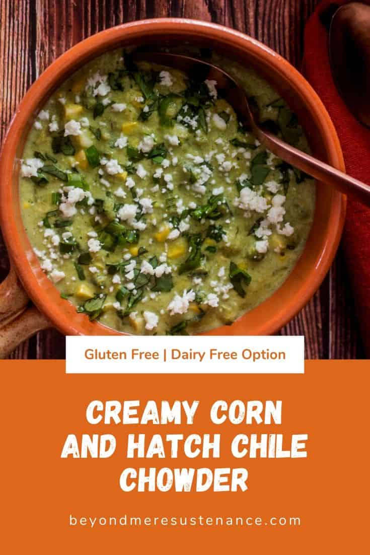 Gluten free corn chowder with green chile in an earthenware bowl, a copper spoon, garnished with cilantro and cotija.