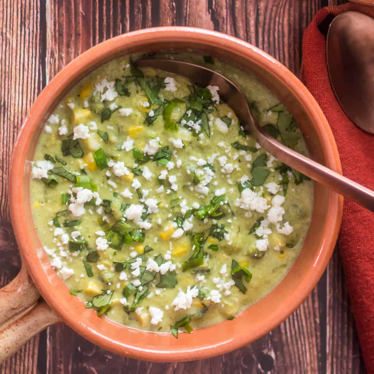 Creamy Corn and Green Chile Chowder in an earthenware bowl on a wood background with a copper spoon.