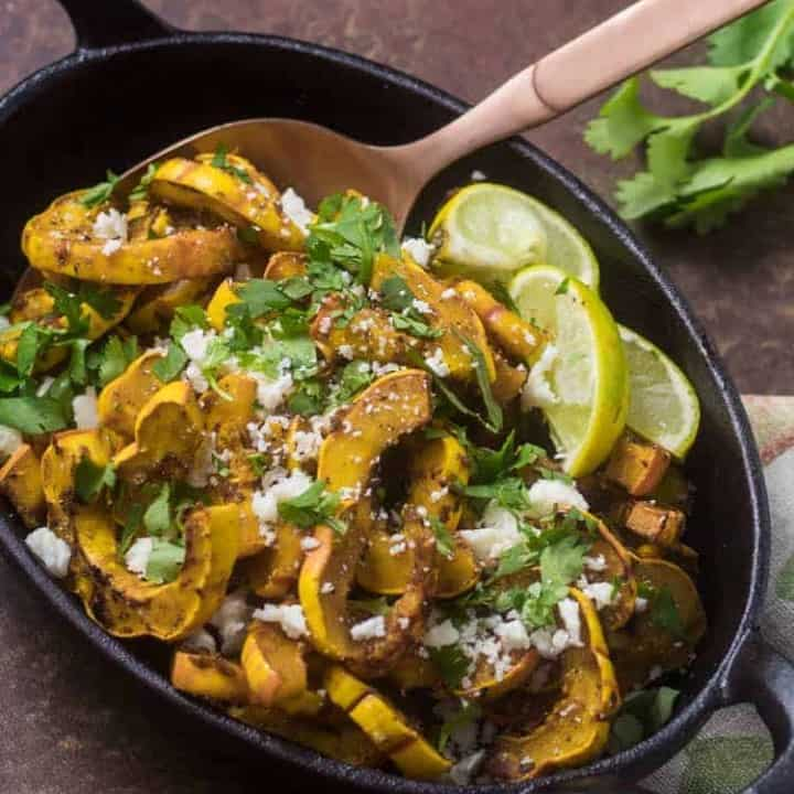 A cast iron casserole with Chipotle Honey Glazed Roasted Delicata Squash with a copper spoon, lime wedges, and fresh cilantro sprig.