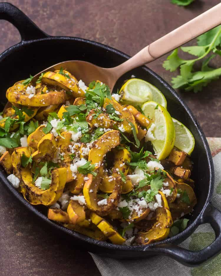 A gluten free vegetarian side dish perfect for your holiday table, chipotle Honey Lime Glazed Roasted Delicata Squash in an oval cast iron skillet with a copper spoon.